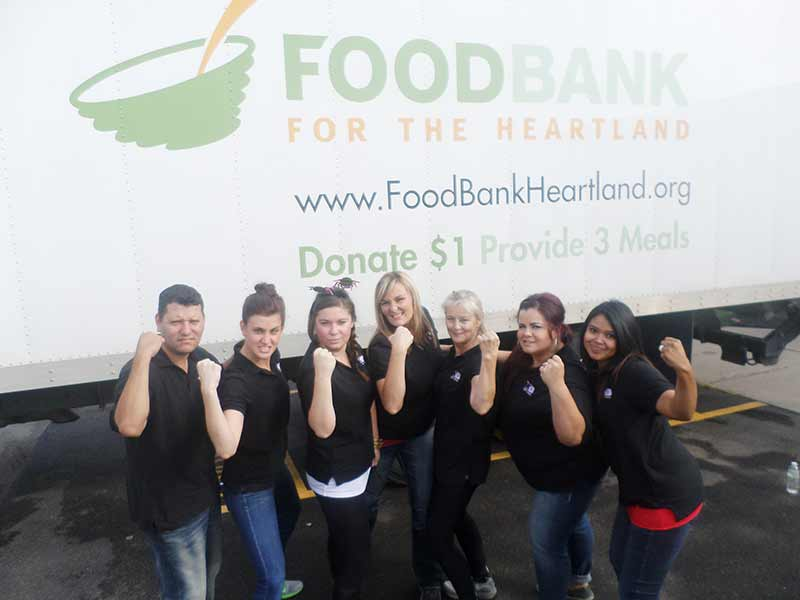 The office team shows off their muscles after packing the Foodbank truck up with barrels of food and cases of water. From the left: Pepe, Tricia, Channing, Kayla, Henrietta, Danielle and Alejandra